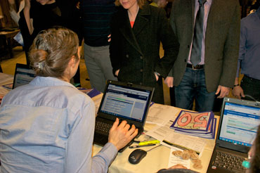 A woman running  a ReadySetAuction check-in station on a laptop talks to the next guests in line.