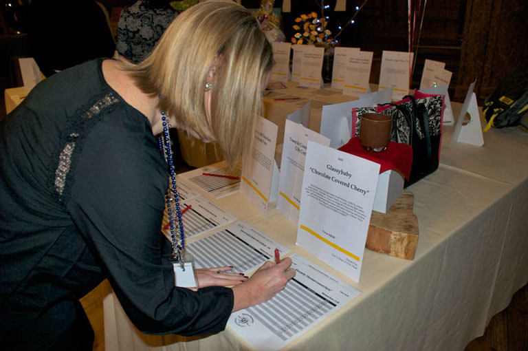 A woman fills in her bid on a ReadySetAuction bid sheet while glancing at a display sheet that describes the auction item.