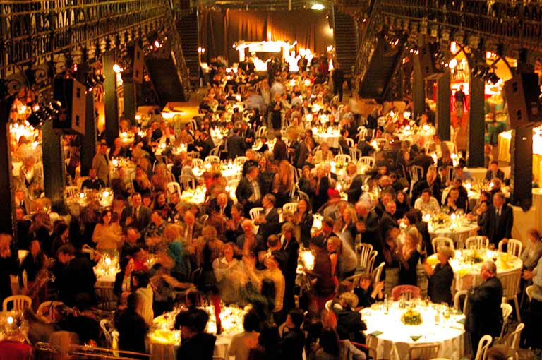 A crowded auction venue filled with gala guests and dining tables: the kind of night that good auction management software makes much easier.